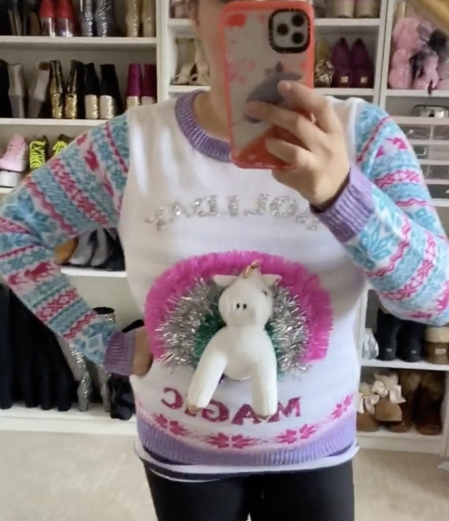A woman in a sweater with a unicorn popping out that says Holiday magic