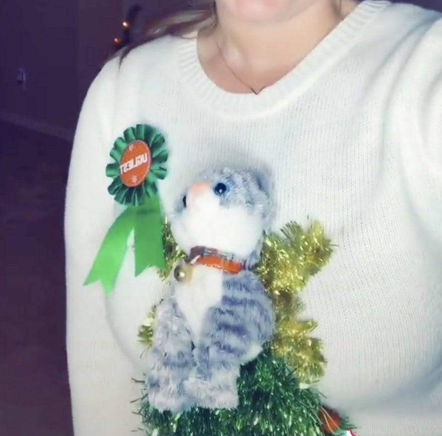 A sweater with a plush cat attached to a tinsel tree