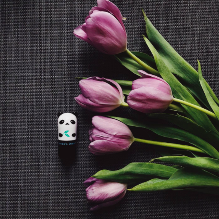 a reviewer photo of the panda-shaped eye stick next to some flowers