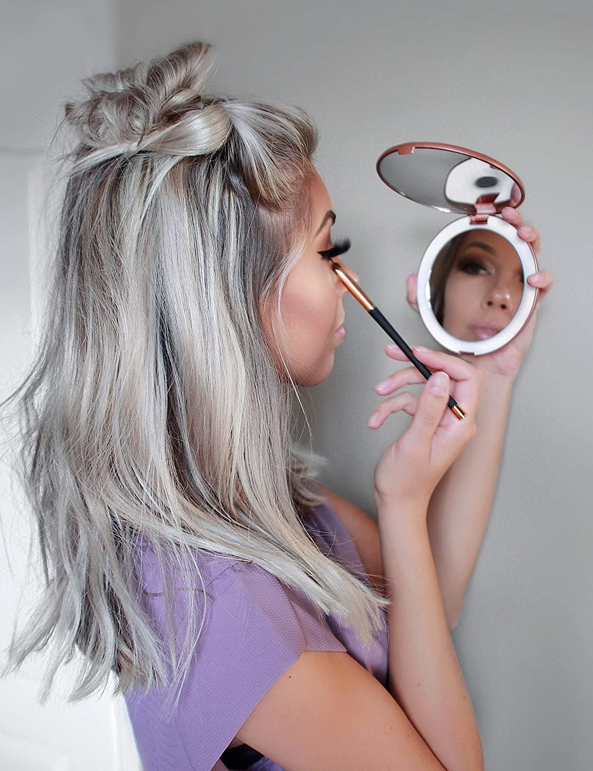 a model using the compact mirror in rose gold