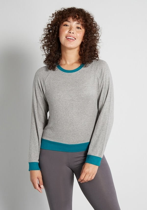 a model wearing the pullover in gray with turquoise detailing