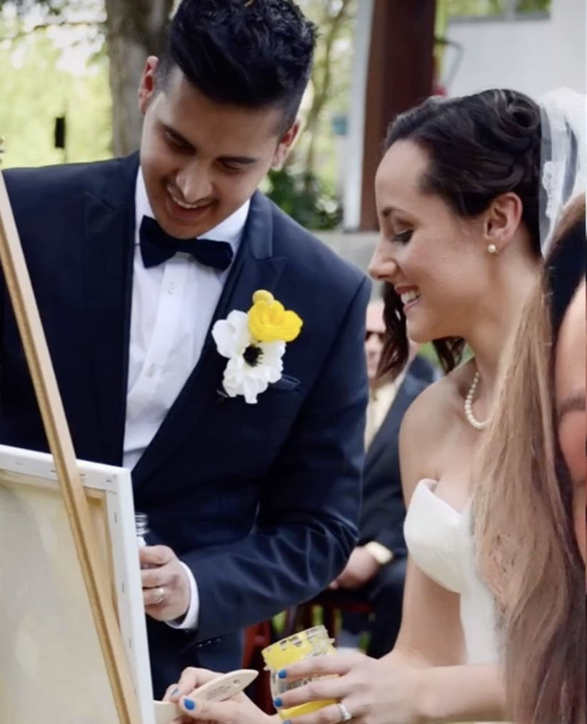 A bride and groom paint during their ceremony
