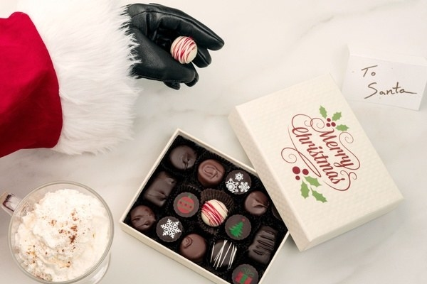 santa hand taking a chocolate out of a box