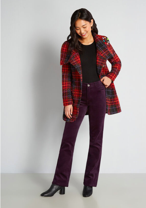 a model wearing the purple pants with a plaid overcoat