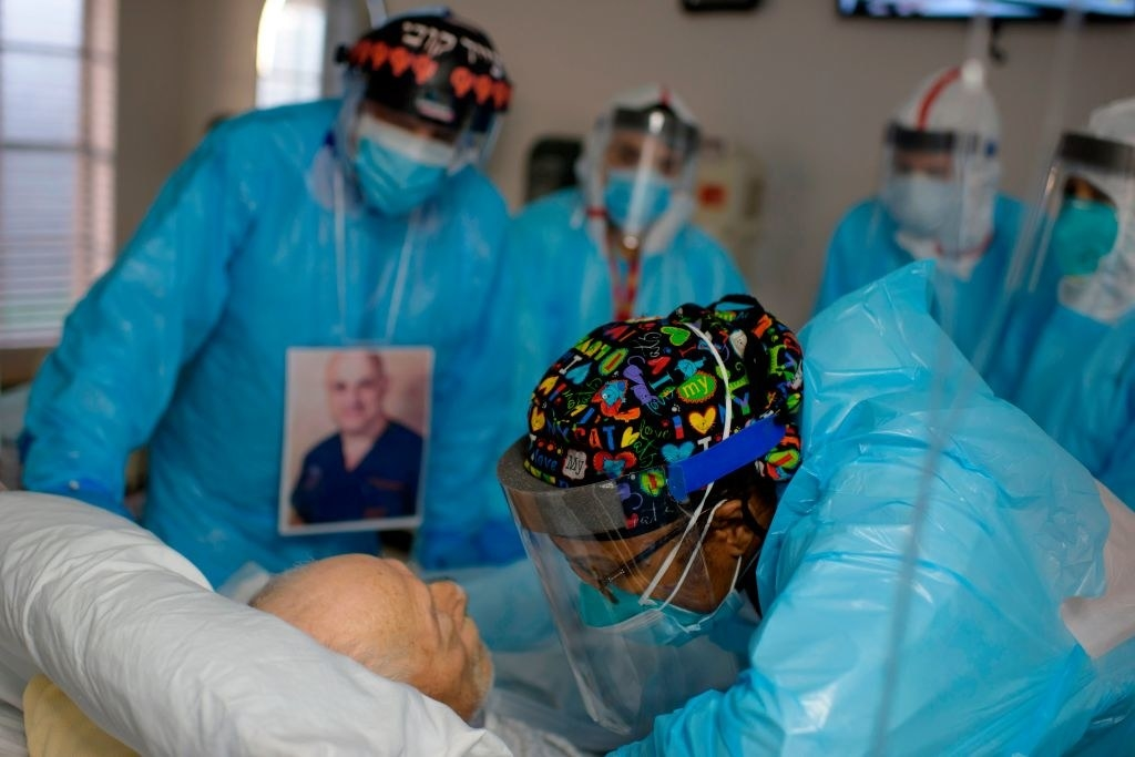 A group of healthcare workers in blue uniforms stand around a hospital bed; one woman wearing a plastic face shield leans over and talks to an older man who is lying in the bed