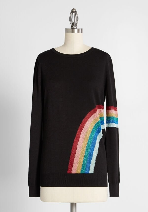 the black sweater with a rainbow on the bottom right side and sleeve of the sweater
