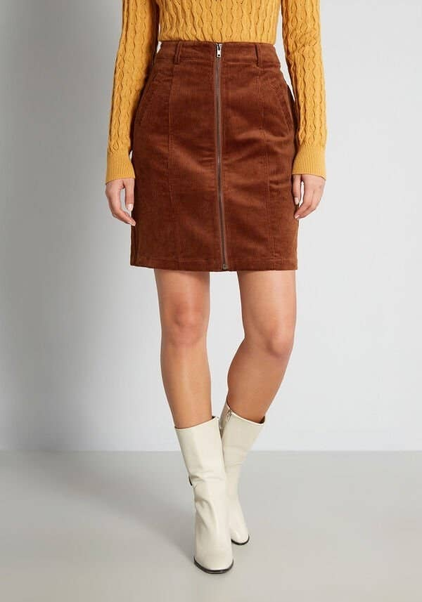 a model wearing the corduroy skirt with white boots and a yellow sweater