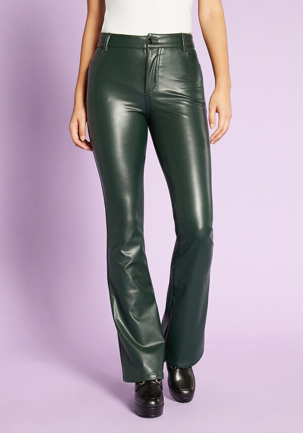 a model wearing the green flare pants which are shiny and gleaming