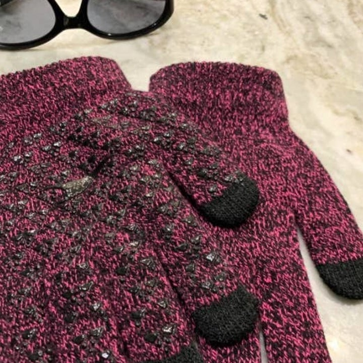 reviewer photo showing purple smartphone gloves next to sunglasses