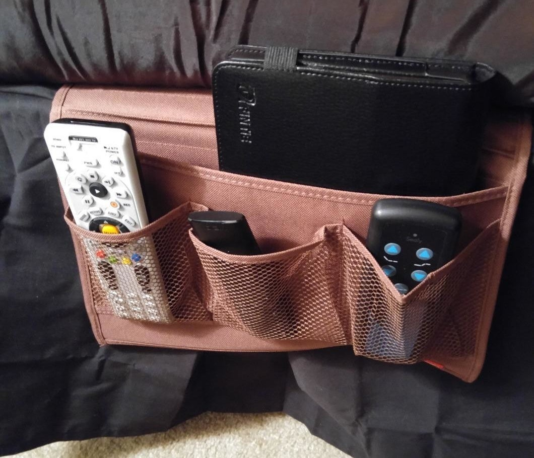 reviewer photo showing bedside caddy with remotes and a book in it