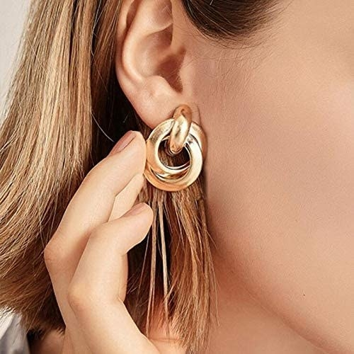 model wearing gold tone statement hoop earrings