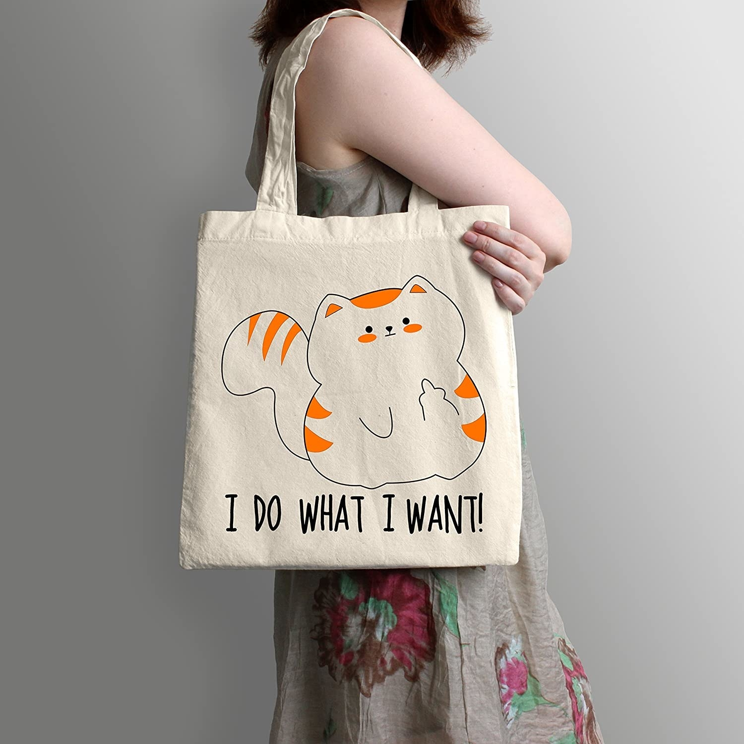 "perosn with tote bag on their arm that says ""do what I want"" with a drawing of a cat"