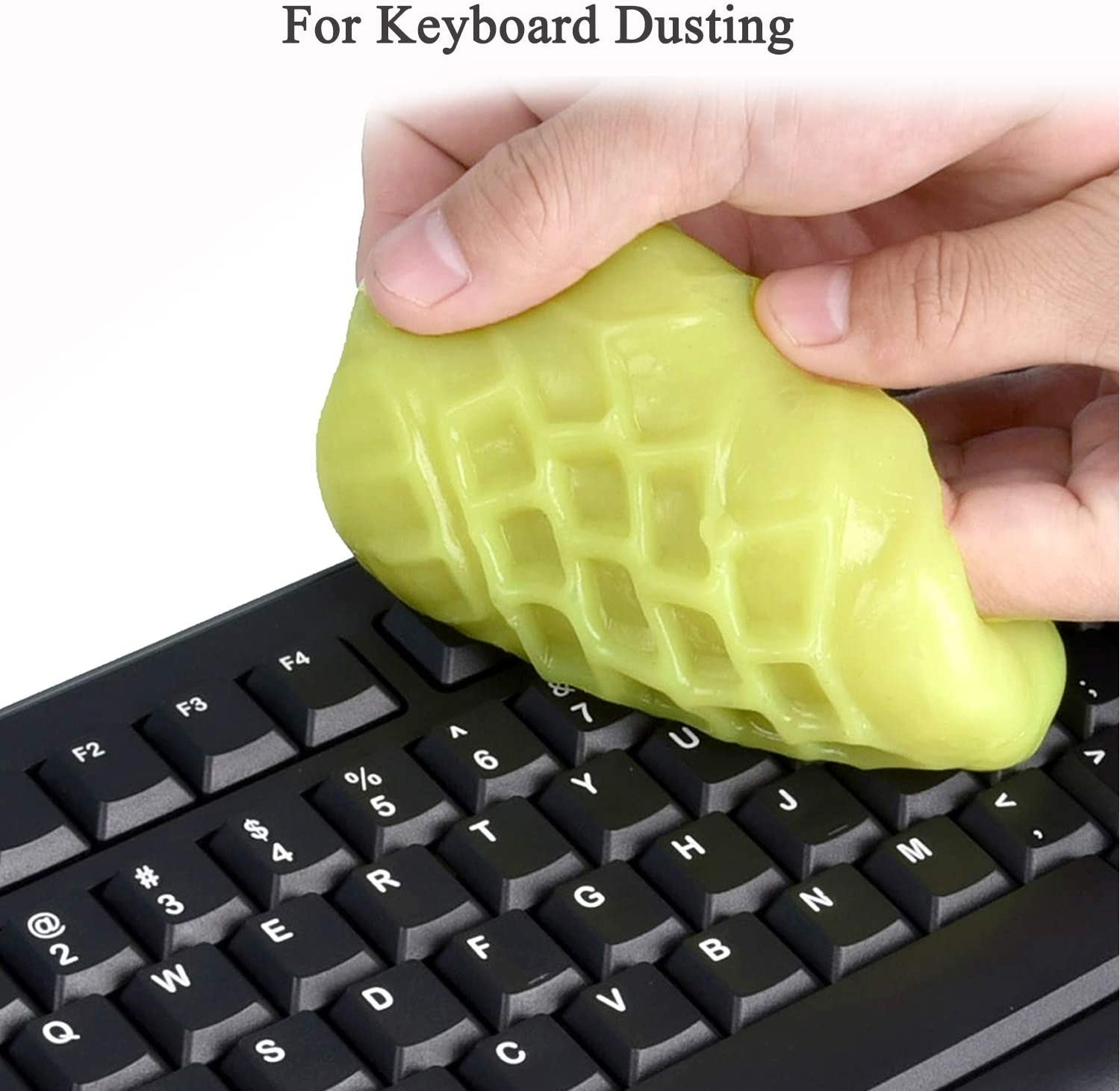 person using the cleaning goo to get in between keyboard keys