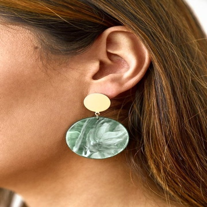 Model wearing the earrings, which have a small gold circle on top and a larger somewhat marbled green circle hanging from that