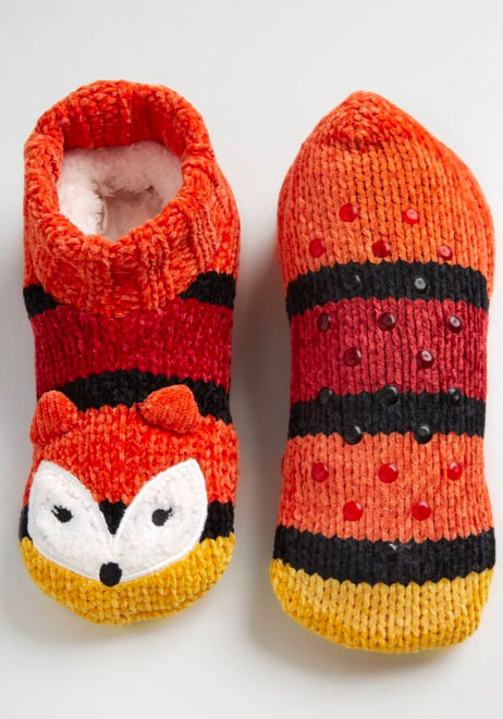 the yellow, white, orange, red, and black fox slippers with faux sherpa insides. one of the slippers is upside down to show the grips on the bottom