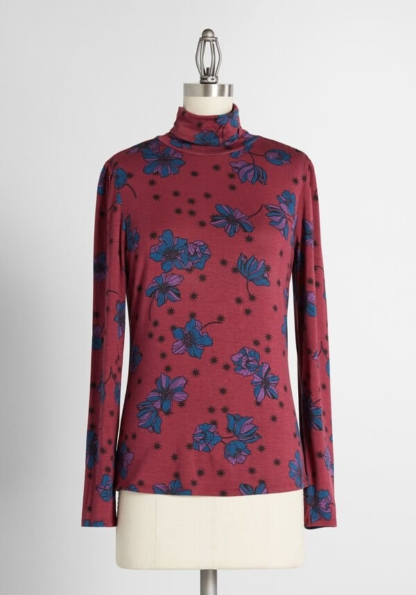 the red turtleneck with a blue, purple, and black floral pattern