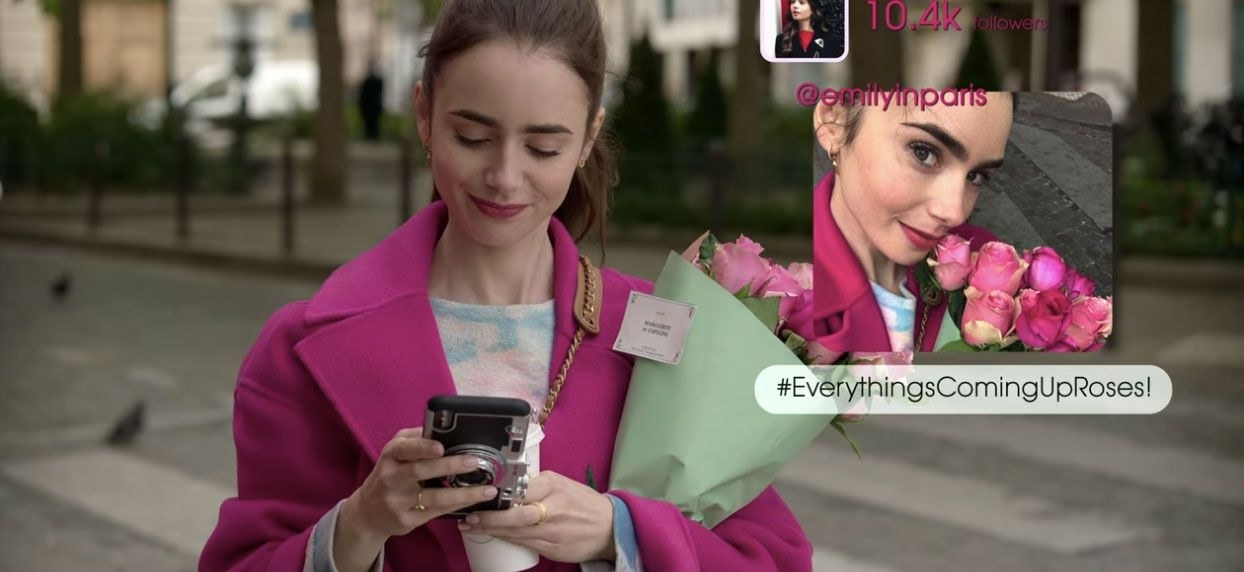 Emily looking at her phone; she has posted a picture of her with roses, captioned #EverythingsComingUpRoses!
