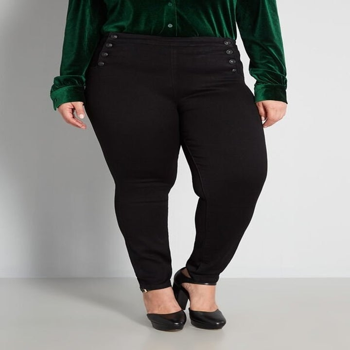 a model wearing the black sailorette jeans with decorative buttons