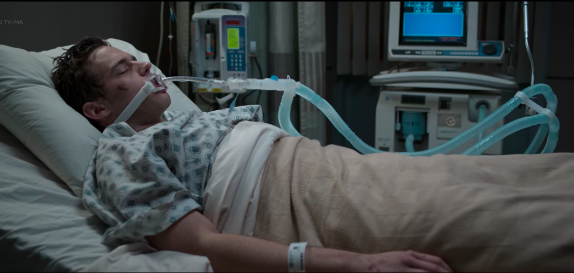 Justin Foley lying in a hospital bed