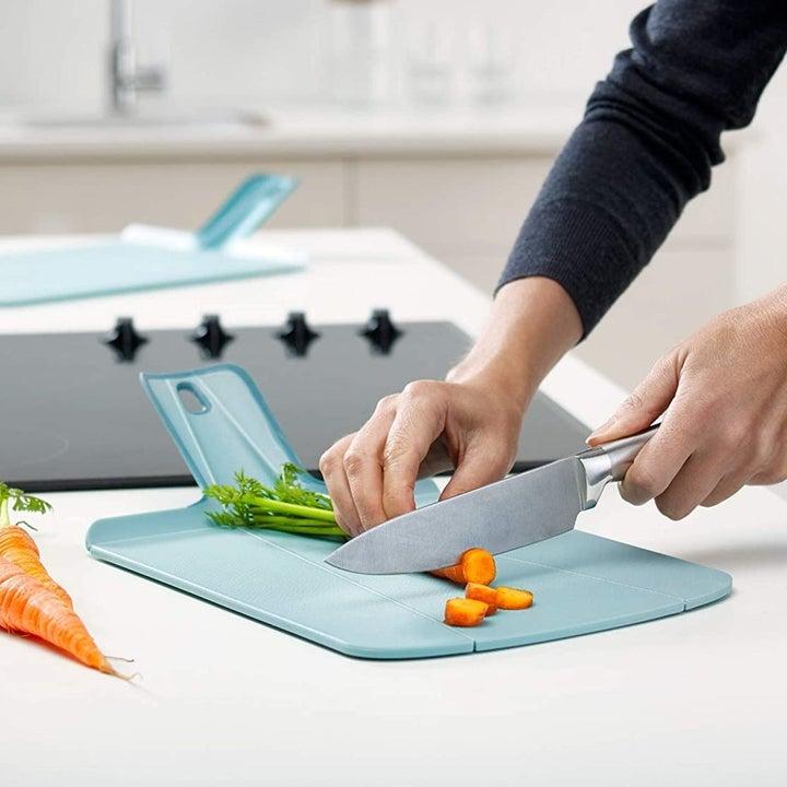 model chopping carrots on blue board