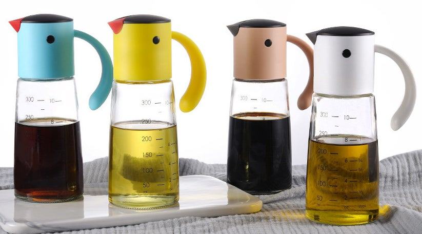 four dispensers with clear bottoms and blue, yellow, pink and white tops