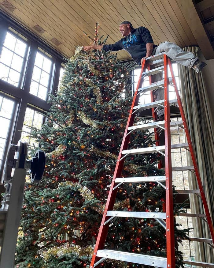 Tim McGraw standing on a ladder, decorating a massive Christmas tree