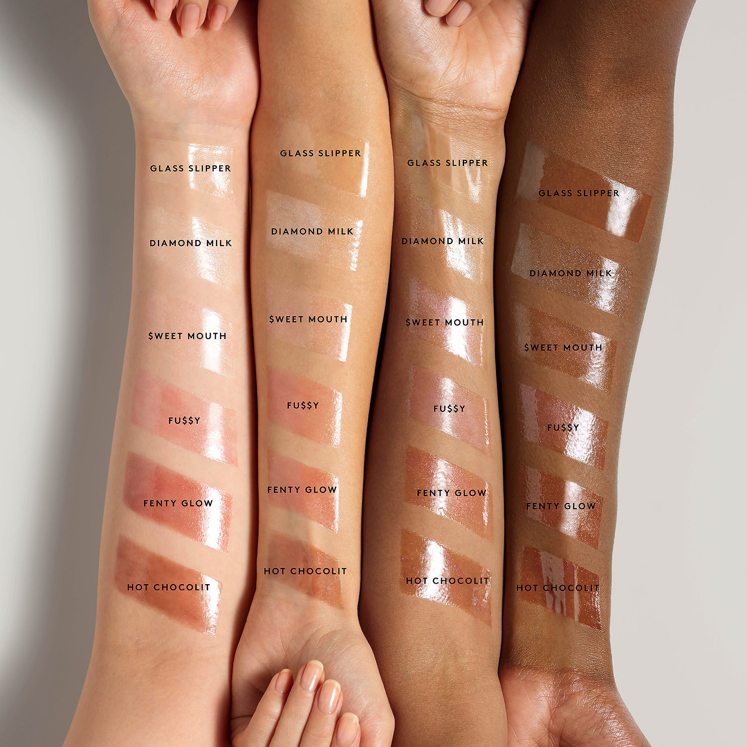 The swatches of glosses on four arms with different skin tones — the gloss colors include pinks, browns, and clears