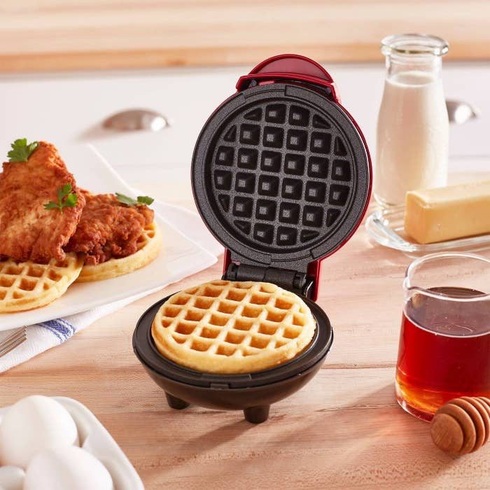 A waffle maker shown open with a waffle inside, on a table with ingredients and a plate of chicken and waffles