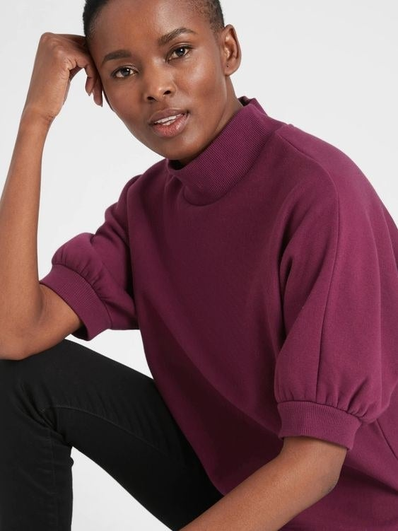Model wearing the maroon sweatshirt with puff sleeves that end at the elbow
