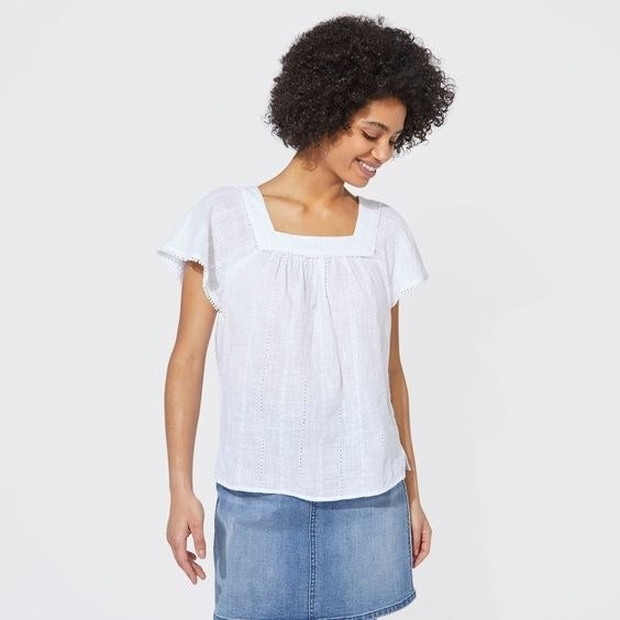 Model wearing the white cotton sleeveless top