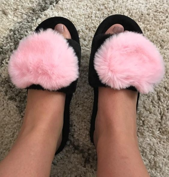 Reviewer wearing the black sandal slippers with big fuzzy hearts