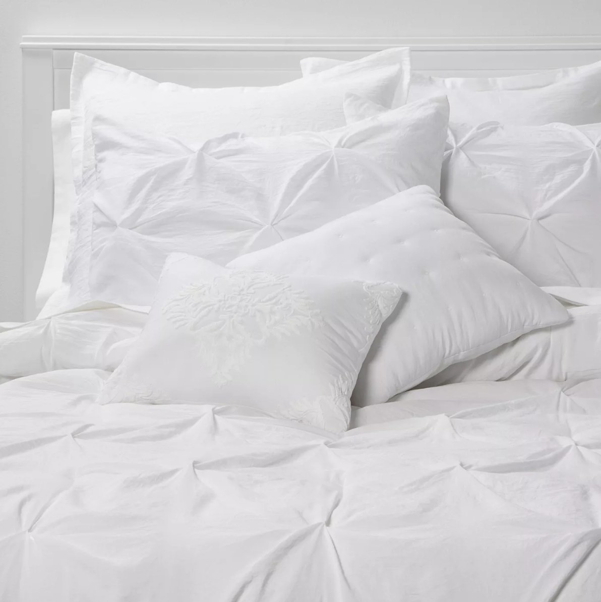 A white pinch pleat comforter with matching pillows