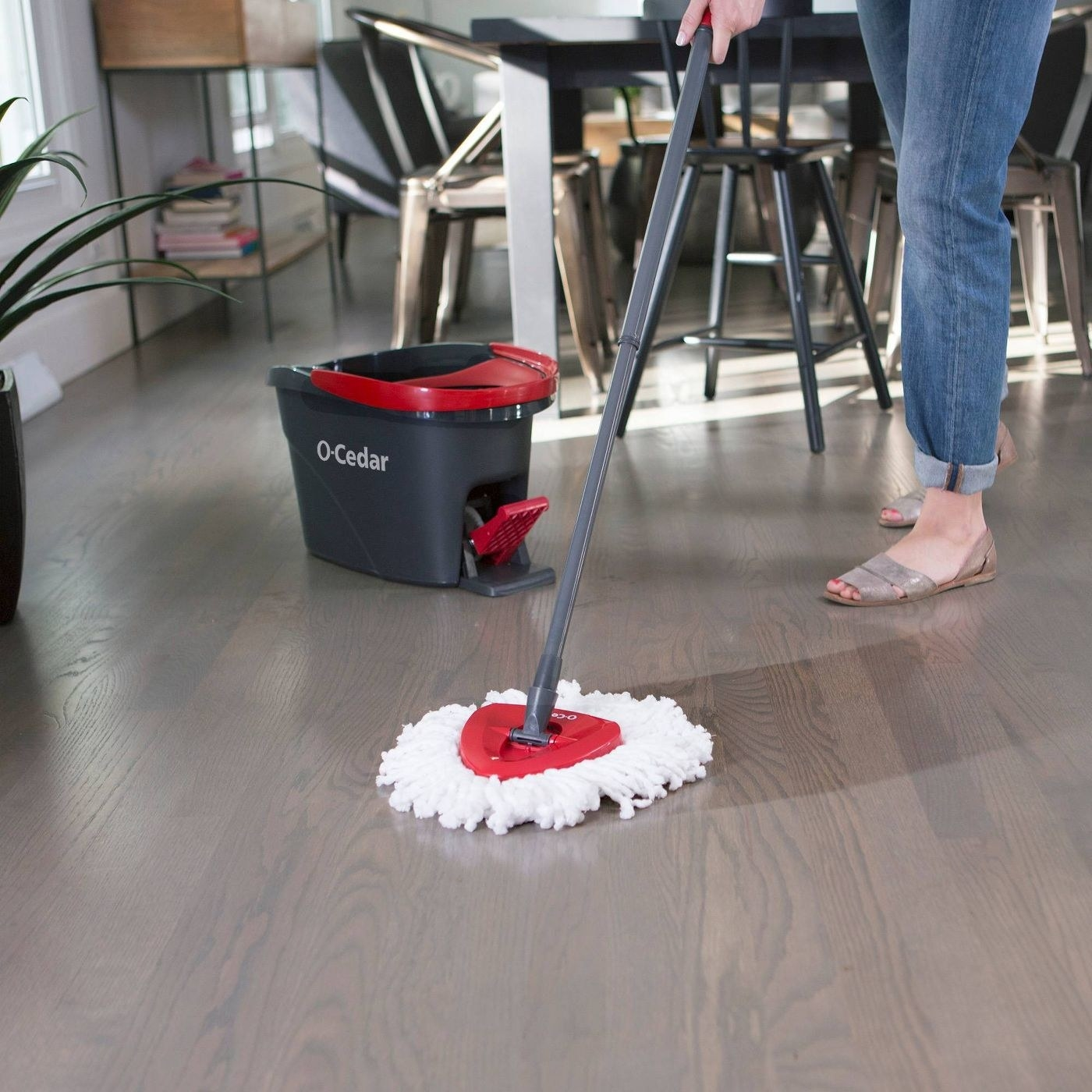 A person using the mop on a wood floor