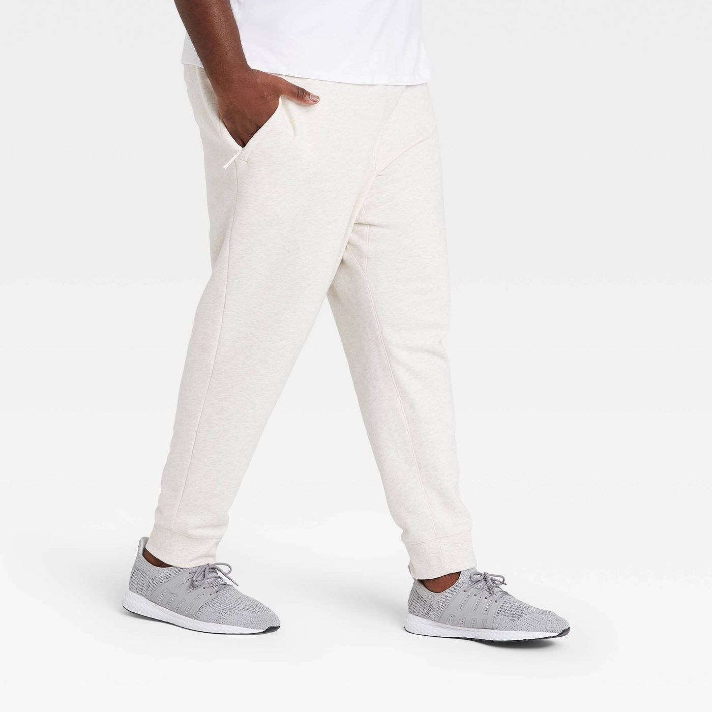 A person wearing white heather joggers, shown against a white background