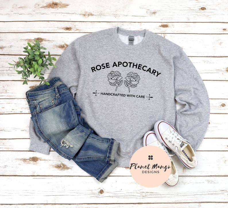 "The sweatshirt with the rose apothecary logo and text ""handcrafted with care"""