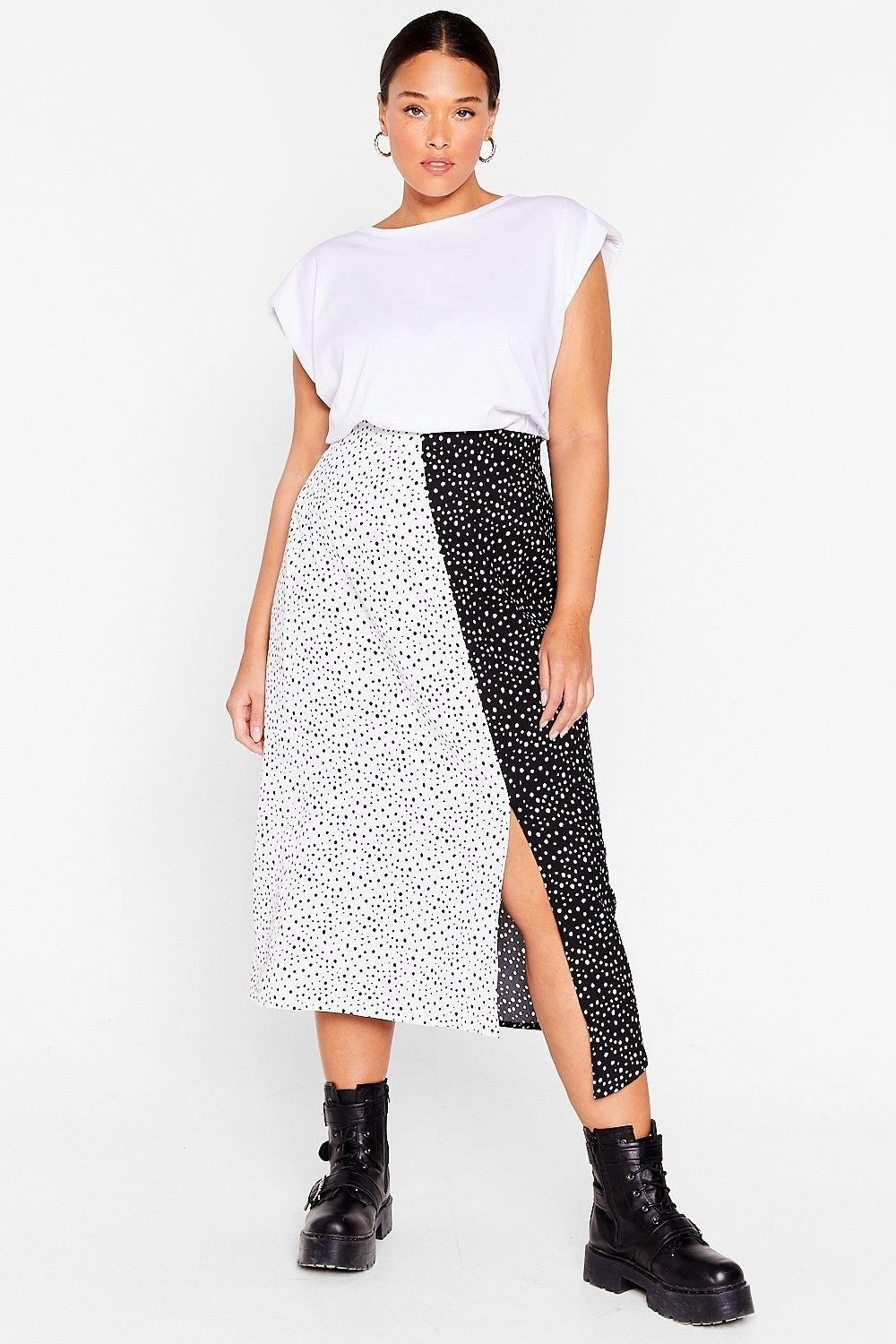 Model wearing the black and white polka dot skirt with small side slit