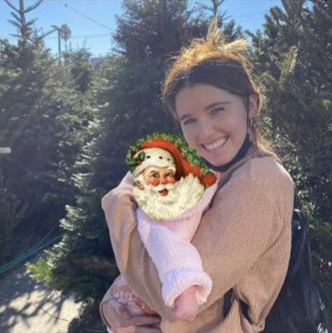 Katherine Schwarzenegger stands in front of Christmas trees, holding a baby, whose face is covered with an image of Santa Claus's face with a hat and beard
