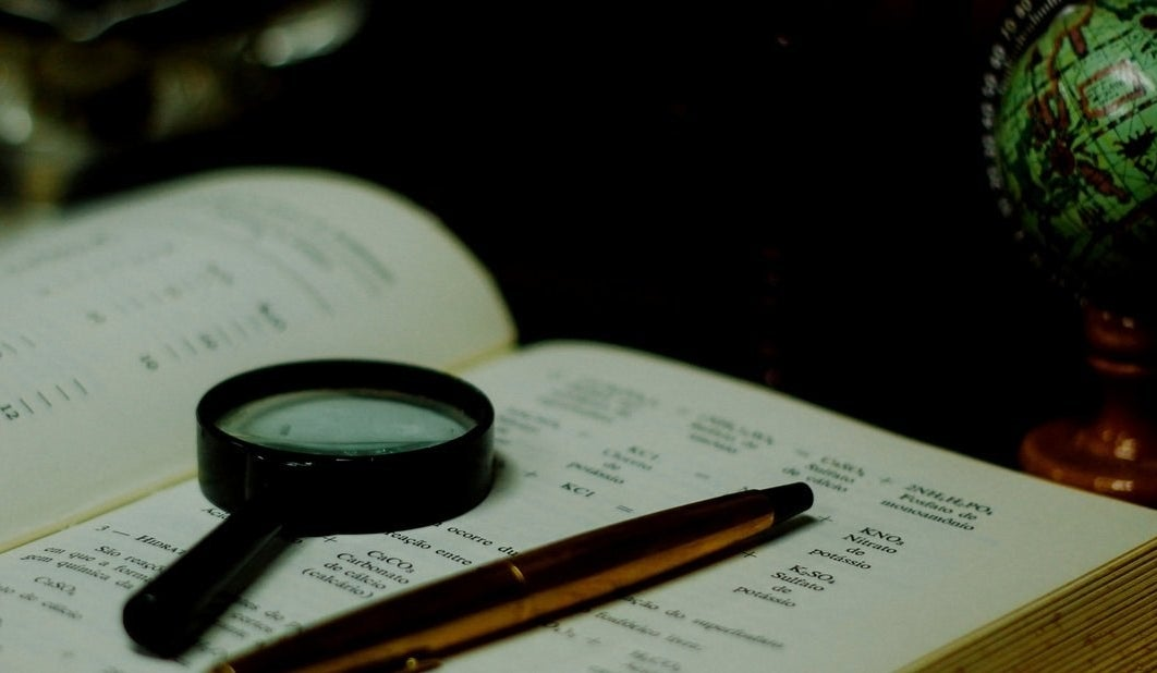 A magnifying glass and pen sitting on a code book