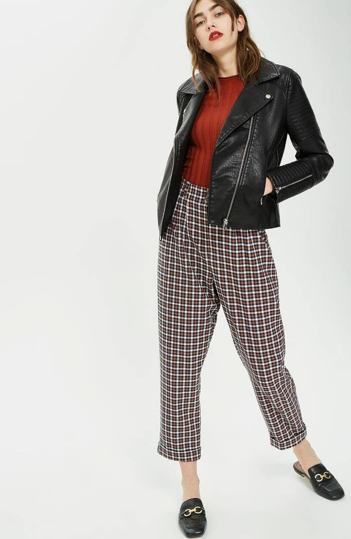 Model wearing the black leather jacket with a red sweater, red check pants, and black loafers