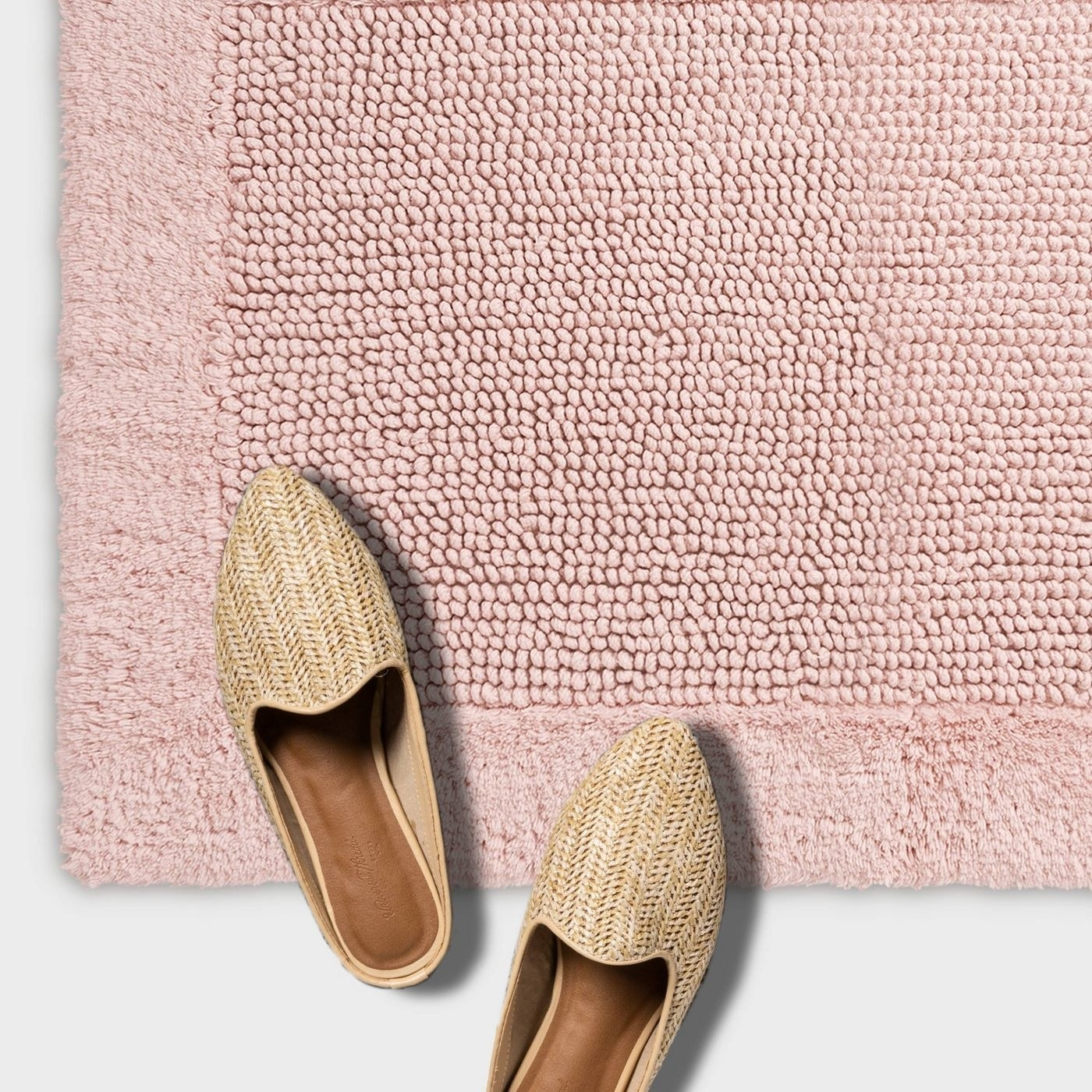 Pink tufted rug with tan slip on shoes resting on it
