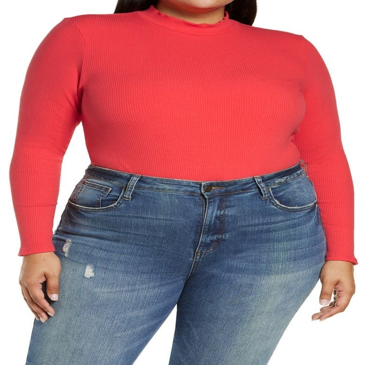 model wearing red sleeved bodysuit with jeans