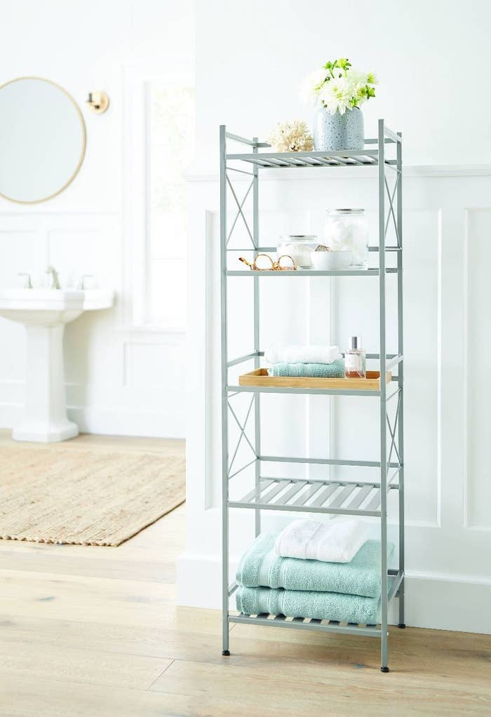 Brushed Nickel shelving unit with aqua and white towels and some bottles displaying cotton balls and flowers