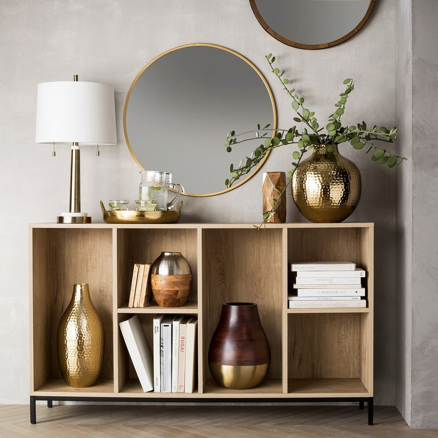 The round mirror in a brass finish, shown above a shelf