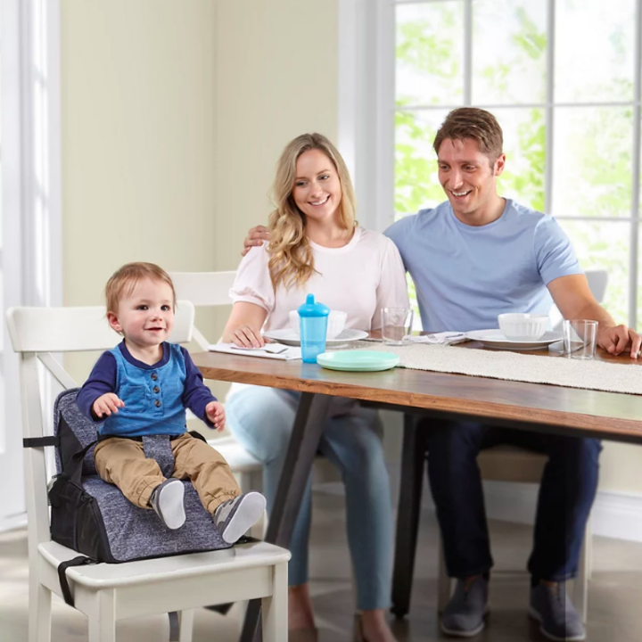 Child sitting on secured booster seat at table with family