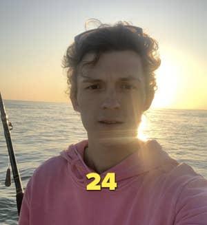 Tom Holland mengambil foto selfie di atas perahu saat matahari terbenam, mengenakan kaus merah muda