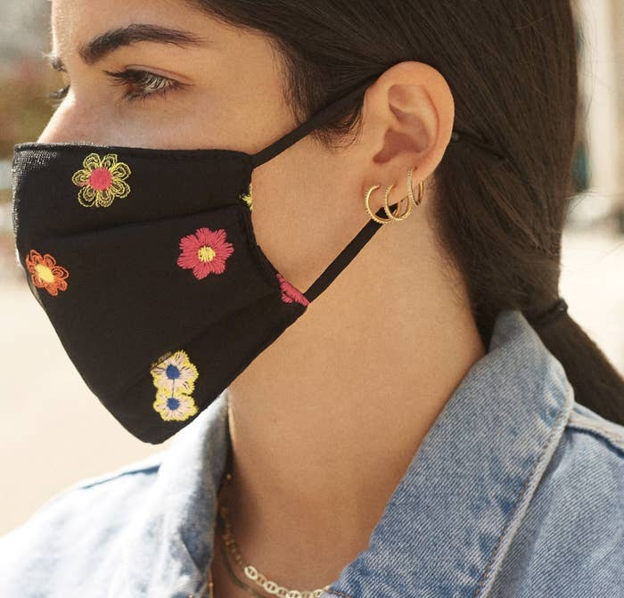 A model in a black face mask with embroidered flowers