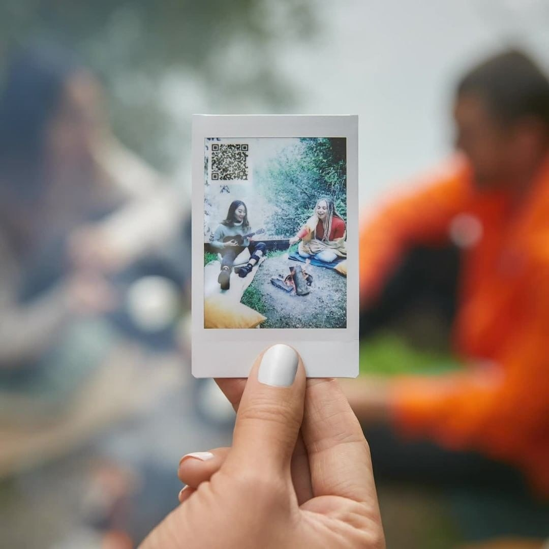 A person holding up an Instax mini picture