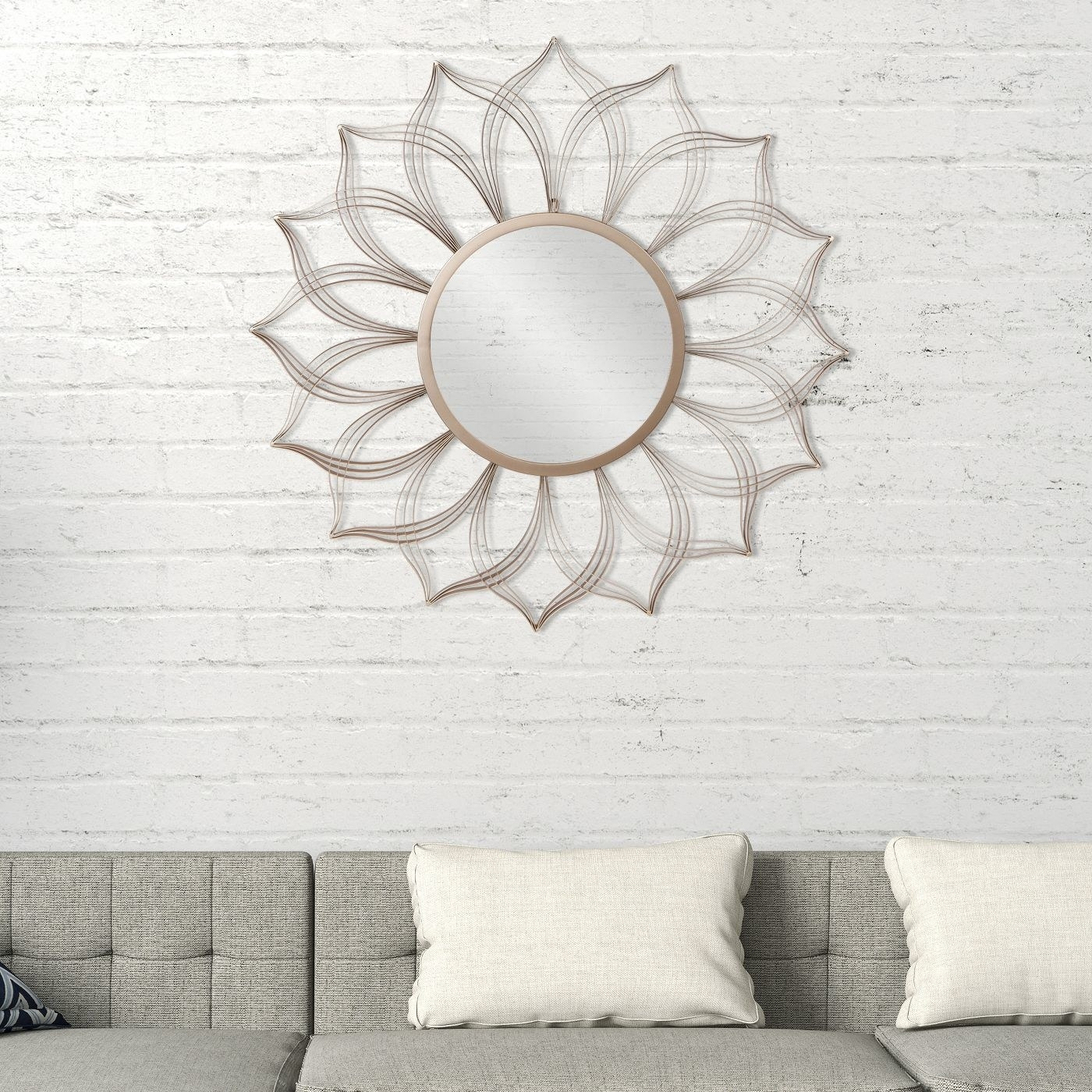 Champagne flower petal mirror on a white brick wall over a gray couch