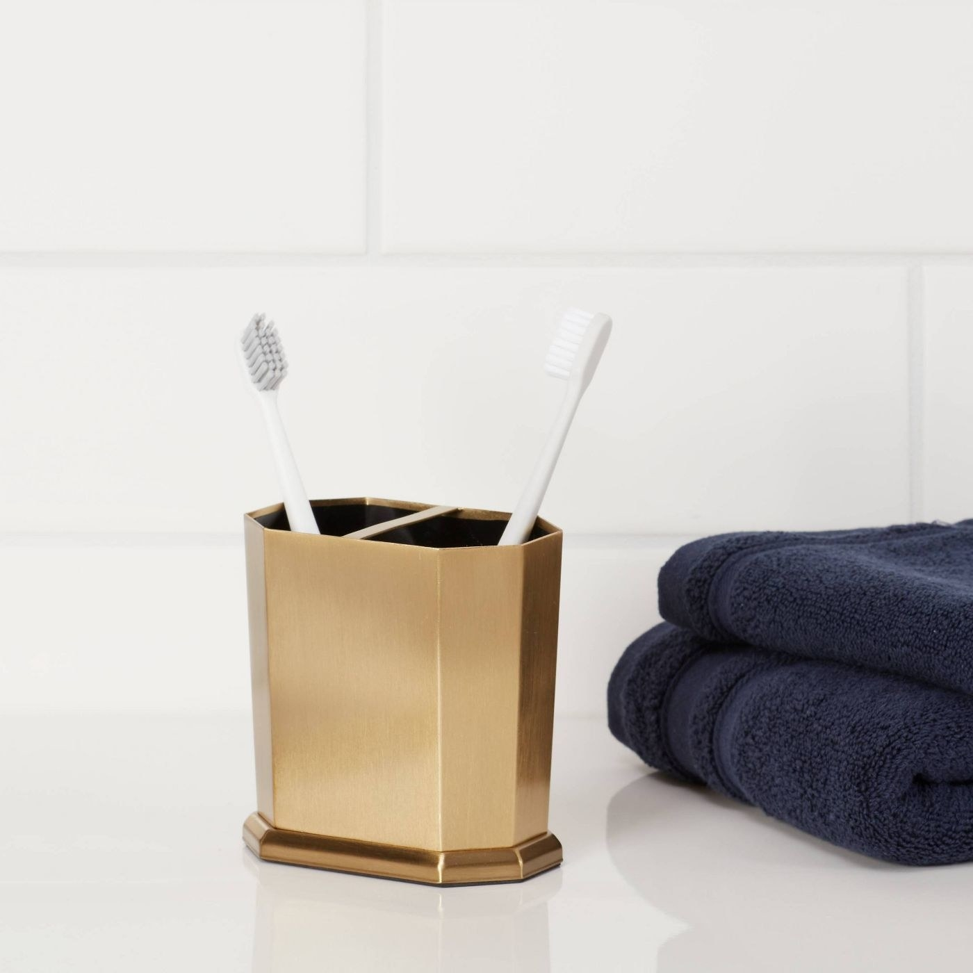 Gold toothbrush holder with white toothbrushes stands beside a navy towel
