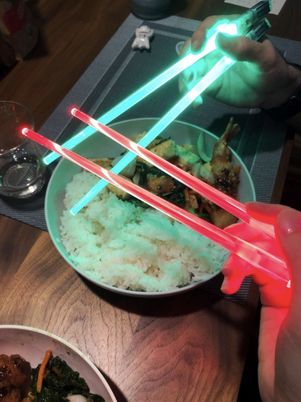 Reviewer using green and red lightsaber chopsticks to eat chicken and rice